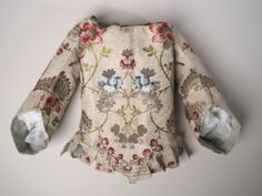 Child's bodice 1730-1740 Cream silk with brocaded pattern in green, plum and red silk, gold and silver thread; lined pale blue silk, with paper stiffening between; fastening at back with bone at each side in lining and holes for lacing; waist cut with narrow tabs bound with cream silk and ribbon; three-quarter length sleeves with shaped sewn-on cuff.