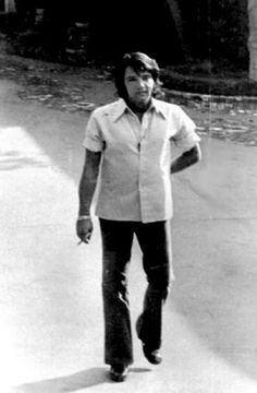 ELVIS WALKING DOWN THE DRIVEWAY AT GRACELAND WHILE SMOKING A CIGAR IN 1970