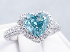 This is our unique 2.35 ctw Heart Shape Diamond Engagement Ring. It has a fascinating 1.80 carat Heart Shape Blue Color/SI1 Clarity (Clarity Enhanced) Center Diamond that looks huge and sparkly. It is set in a sophisticated 14K White Gold setting with a halo and pave set diamonds that travel halfway down the band. This ring is listed for just $6,490.