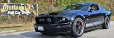 Black 2007 Mustang GT with Steeda stripes, Steeda spoiler, Cervinis concept hood, Silver horse racing flush mount louvers, billet fuel door, billet grills and Axis Sport XGT wheels with red brake calipers and cross drilled rotors.