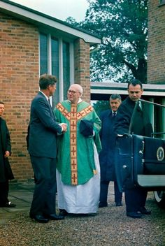 "1963. 30 Juin. By Robert KNUDSEN. KN-C29353. JFK in England. President John F. Kennedy shakes hands with Father Charles P. Dolman before entering the Presidential limousine (Lincoln-Mercury Continental) following mass at Our Lady of the Forest Church, Forest Row, England. Also pictured: White House Secret Service agents, Win Lawson (far left), Gerald A. ""Jerry"" Behn (right of Father Dolman), and Ken Wiesman (holding open car door)"