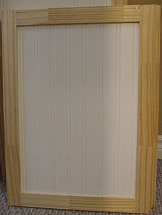 Add trim and paintable beadboard wallpaper to old kitchen cabinet doors for a wonderful make-over!