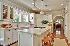 kitchen - subway tile, marble counters, pendants, canned lights, lights under cabinets, frig on corner