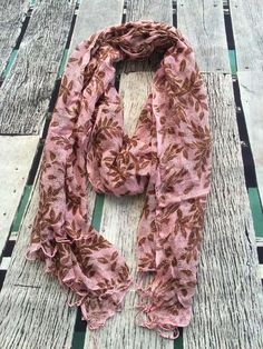 Beautiful leaf in contrasting colours scattered across this gorgeous light weight loose weave summer scarf in soft pink and chocolate brown