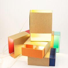 Lampe (ou applique) conçue comme une boite d'allumettes dont l'intérieur est en papier de couleur turquoise (certifié par le FSC- Forest Stewardship Council) et dont l'extérieur est en carton re...