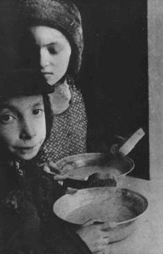 Crianças judias com tigelas de sopa no gueto de Varsóvia. Varsóvia, Polônia, por volta de 1940.