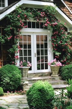 Inviting home entrance with climbing roses and potted annual flowers. Hardscape walks flanked by boxwoods give the entrance an elegant feel.  In Birmingham, AL, for awesome service on your sprinkler and landscape lighting, www.BlueSkyRain.com. #sprinkler #garden #irrigation #landscape