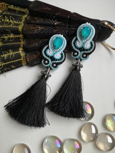 Candy blue cabochon surrounded by black and white soutache and completed with black tassels