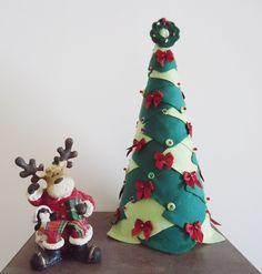 PRONTA ENTREGA.    Árvore de Natal de Mesa, formato cone, patchcolagem em feltro nas cores: Verde Pinheiro e Verde Pistache Claro, aplicação de miçangas vitrificadas na cor Vermelho, lantejoulas irisadas na cor Verde e laços em cetim na cor Vermelho, no topo da árvore uma guirlanda em feltro na cor Verde Pinheiro.    Medida: 31 cm alt x 13 cm base    Obs.: rena em resina não acompanha o produto. R$ 45,00