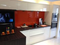 Here's a nice neat little white gloss kitchen recently installed by us,with orange glass back splash and floating wall shelves,ideal for a small kitchen area but has everything you need at your fingertips,even a plasma TV!!!