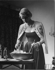 New York, 1949 by Nina Leen 40s 50s woman prepares salad dress full skirt sweater shoulders chunky chain bracelet with medallion charm peso
