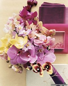 The contrast of bright yellow and deep purple gives this daring, exotic bouquet -- composed of miltonia and phalaenopsis orchids -- a modern yet playful feel. The stems are bound with velvet ribbon and thin metallic trim.