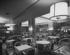 The cavernous First Class Dining Room on the RMS Queen Elizabeth. The absence of table dressings is suspicious: it leads to the question of whether this image was taken upon her (rushed) completion in 1938, or during her post-War restoration to passenger service.