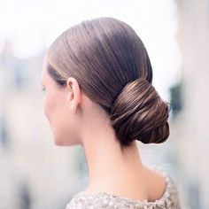 Put your hair into a low pony bun, then wrap the remaining hair around the knot for a subtle modern chignon hairstyle.