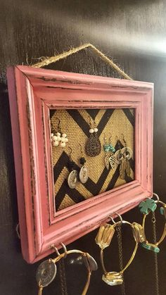 This jewelry organizer is made from an upcycled picture frame. It has been painted dark gray with pink over it and distressed. The backing is wire mesh with chevron burlap on top that makes it perfect for hanging earrings. The bottom has 3 hooks for hanging necklaces or bracelets. Overall frame size is 9.5x7.5 Total burlap size is 5x7. It has a piece of jute twine for hanging. *Jewelry not included*