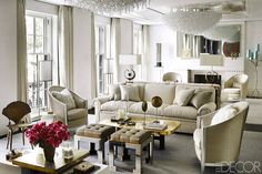 The living room's armchairs, and sofa are covered in a customized barely-gold brocade. The understated hue keeps the bold gold coffee table and statement chandeliers from overwhelming the space. Tour the rest of the home.   - HarpersBAZAAR.com