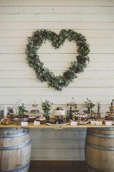 eucalyptus wreath in heart shape behind cake table
