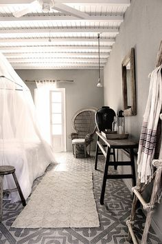 Moroccan bedroom. Mosaic tile floors and light neutral palette.