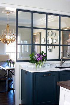 Beautiful kitchen features blue cabinets adorned with brass hardware paired with white marble countertop fitted with a wide stainless steel sink and a gooseneck faucet placed under a glass divider which overlooks the dining room.