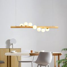 Featuring the sleek linear design and spiralling arrangement of glass shades, this charming Tram Lighting Collection will illuminate your home with a modern flair. Playful and minimal, this light fixture features globe shades spiral around a slim woo