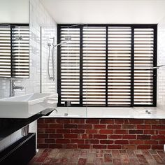 White inbuilt bathtub with exposed red brick wall and floor, white square stand alone basin on black floating vanity, chrome tap and mixer, chrome shower head unit, white subway tiled walls, matte black blinds. Project by - @sussextaps and @wolveridge #taps #interiordesign #bathroom #australia #architecture #bathroomdesign #bathroomcollective Visit our website for more www.bathroomcollective.com.au