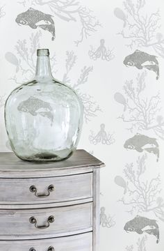 An elegant all over wallpaper design featuring motifs of coral, Koi carp and Octopuses with metallic detailing.