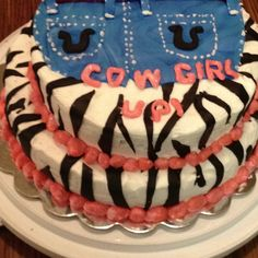 Client wanted a chocolate and a white cake zebra print trimmed in pink blue jean shorts black horse shoes and cow girl up on it