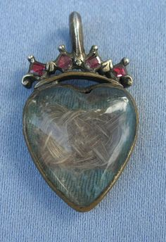 Mid 18th century mourning pendant with garnet crown and hair work encased in crystal.