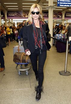 Kate Moss wears a black top, belted black pants, a button-down printed blouse, skinny scarf, a blazer, and black fringe boots