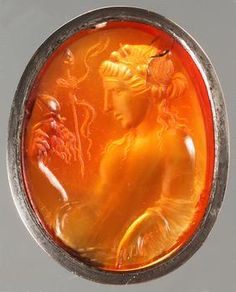 An ancient Roman carnelian gem depicting the god Bacchus holding his symbolic attributes, a mask of Silenus and a thyrsus. (Kunsthistorisches Museum Vienna)