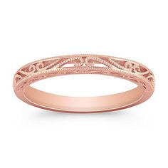 This romantic wedding band is crafted in quality 14 karat rose gold. The migrain detailing gives the design a vintage feel.