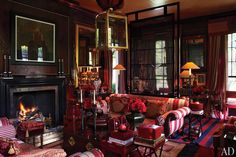 """Anouska Hempel's English Country House - In the sitting room, a lantern designed by Hempel for Charles Edwards hangs above Regency sofas covered in a striped linen. The mixed-media work over the fireplace is from Robert Heindel's """"The Protecting Veil"""" series, and the Javanese-inspired slatted screen was custom made."""