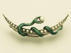 A fine and impressive antique Victorian ruby and pearl, 15 carat yellow gold, green enamel snake crescent brooch.