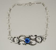 Sterling Silver Filigree Inspired Chain Bracelet with a Faceted Genuine Blue Quartz Accented with White Moonstone The Silver Dragon- Bracelets. $65.00. Designed And Hand- Crafted in Sterling Silver. This Bracelet Fits a Standard Woman's Wrist. This Unique Bracelet is Created only after Your Order Arrives. Please Allow 7-10 days for Delivery.. This Bracelet was Designed by The Silver Dragon, a Jewelry Shop in New England. Thank you for Supporting American Business.. ...