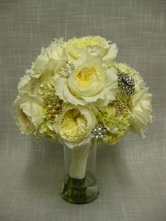 Bridal bouquet of David Austin Patience roses, cream hydrangea and vintage broaches with a satin and lace stem wrap.