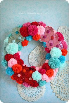 Make a Christmas wreath with pom poms.