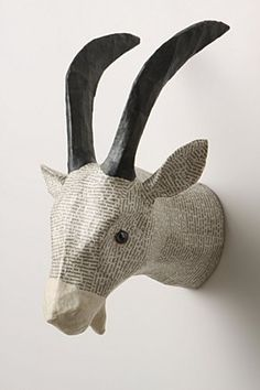 Layers of repurposed cement bags are covered with vintage French book pages to create this handmade, papier mache animal head.