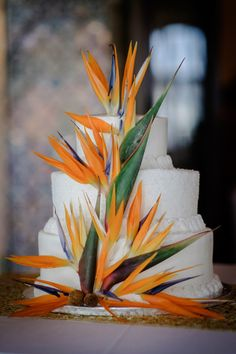 Tropical wedding cake idea - three-tier white frosted wedding cake with bright birds of paradise {Artsinfotos Photography}
