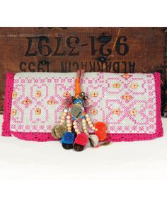 """Ethnic crossstitching in bright colors with natural beads and jute makes this clutch the ultimate finishing touch to a resort outfit10""""x5""""x1.5"""""""