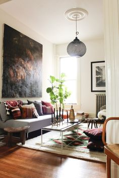 Small living room, massive painting - love the indoor plants and the warm feel!