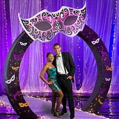 The Masquerade Ball Arch Decorations feature a giant pink and purple cardboard mask, and thirty-six smaller mask cutouts.