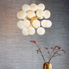 Modern 'Mid Century' pendant ceiling light with brushed gold finish.  Height: 72cm - 163.5cm Diameter: 55cm Maximum Wattage: 3w Light Bulb: 28 x G9 LED Light Bulbs A timeless and modern design with a 'mid-century' feel, this impressive pendant light is at home in modern or classic interiors. Finished in an 'on-trend' brushed gold finish with gloss white glass shades and suspended from height adjustable thin wire cable with clear flex.