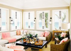 Beige walls, brown woven couch and chairs with white cushions, printed orange, pink, and white throw pillows, pink throw blankets, black coffee table, and white lamp