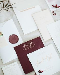 Deckle-edged save-the-dates were foil-printed in rose gold and mailed out in burgundy envelopes, all designed by Amber Moon Design. This was the first introduction of calligraphy by Anne Robin, which reappeared throughout the stationery and event itself, including the oversized wax seal affixed to the invitation's petal-fold enclosure.