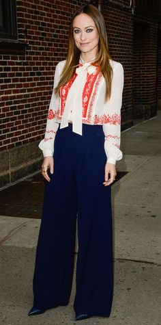 For an appearance on The Late Show with Stephen Colbert, Olivia Wilde selected a pretty red-embroidered tie-neck blouse and navy wide-leg pants, with black Casadei pumps.