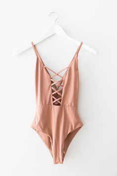 Seamless one piece swimsuit with a caged front in dusty rose. Cheeky fit with high leg cut sides. Open square back with adjustable straps. Made and manufactured in the USA at the highest quality stand