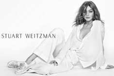 Stunning: A second shot sees Gigi sitting in a lightweight white ensemble which hangs elegantly off her slender frame and a pair of embellished Décor sneakers