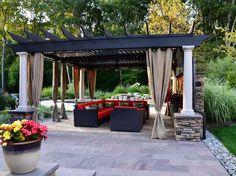 pergola contemporaine avec rideaux taupe aménagée avec un salon de jardin en résine tressée