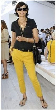 Ines de la Fressange in a black shirt and yellow pants.