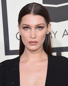 Bella Hadid's simple makeup look of contoured cheeks, subtle brown smoke eye with super sleek, middle part hairdo.